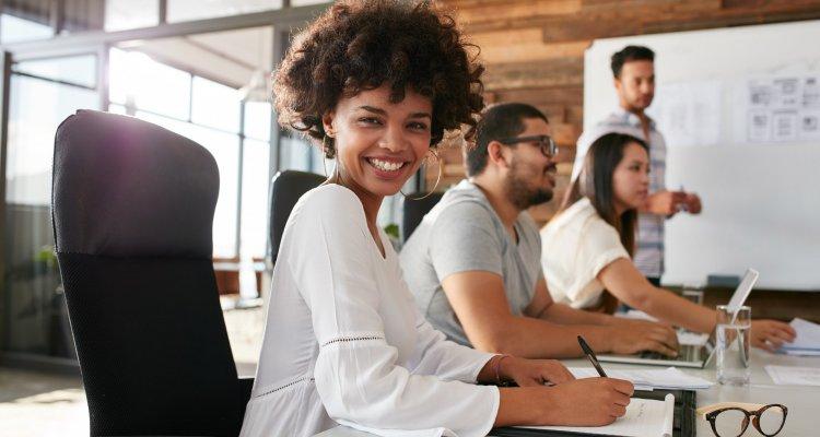 executiva sorridente sentada à mesa de reunião com outros colegas de trabalho