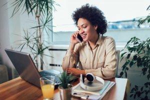 Executiva no seu ambiente de trabalho home office fala ao celular