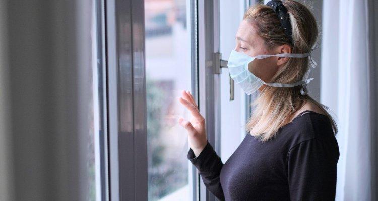 mulher com uma máscara no rosto observa o movimento da rua de sua janela