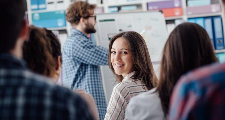 aluna olha para trás e sorri enquanto o professor está lecionando