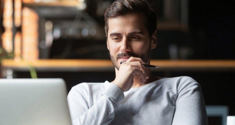 Homem olhando para o seu notebook e refletindo com a mão no rosto e uma caneta entre os dedos.