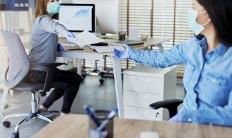 Duas profissionais do ambiente de trabalho protegidas com luvas e máscaras, uma passa uma folha de sulfite à outra.