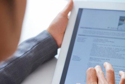 Headhunter olhando curriículo em um tablet.