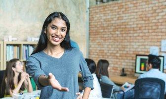 Profissional trans estende a mão ao fundo colegas de trabalho atuam num escritório descolado