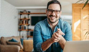 Homem sorridente em sua casa com o seu notebook