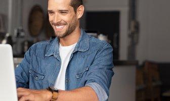 Homem sorrindo usando laptop