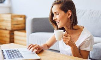 Mulher jovem tomando cafe e olhando para o seu notebook sorridente