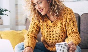Mulher tomando cafe e trabalhando no notebook sentada no sofá da sua casa
