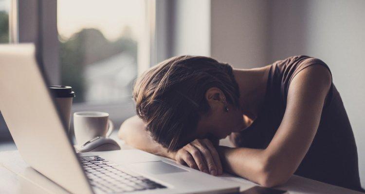 Executiva se debruça à frente de um notebook com ar de cansada
