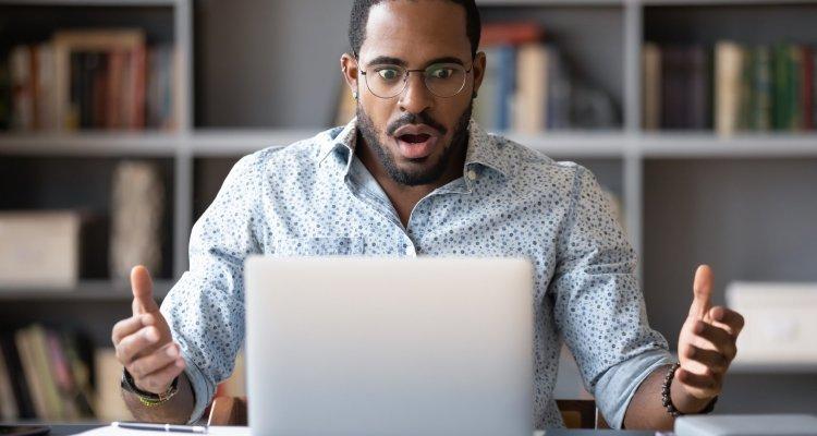 executivo negro com expressão de assustado à frente do computador