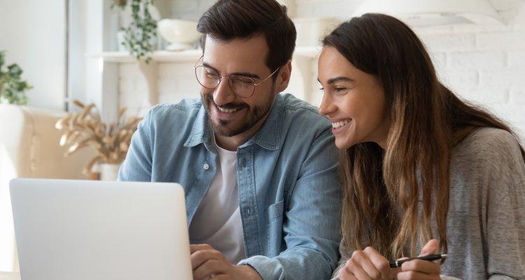 Um homem e uma mulher jovens felizes olhando para o notebook do homem
