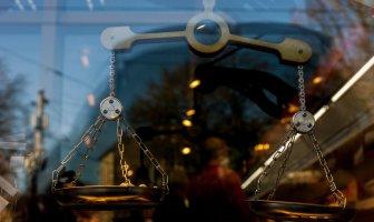 Numa vitrine espelhada, aparece uma balança desigual, ao fundo pessoas com máscaras