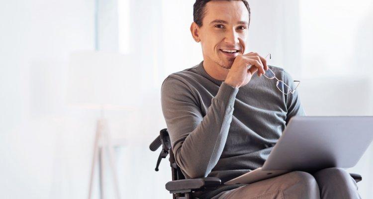 Homem sorrindo em cadeira de rodas