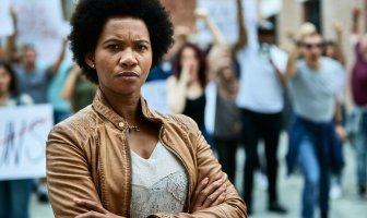 mulher negra com braços cruzados, atrás dela há um protesto