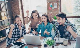 jovens executivos vibrando na frente da tela de um notebook