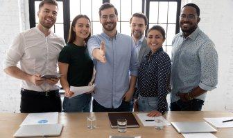 Jovens executivos atrás de uma mesa, um deles estende a mão em direção a câmera