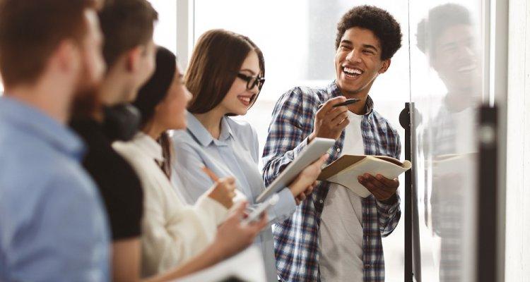 Em frente a uma lousa, executivos jovens, segurando seus cadernos, sorriem.