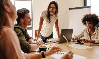 jovens executivos ao redor de uma mesa de reunião sorrindo