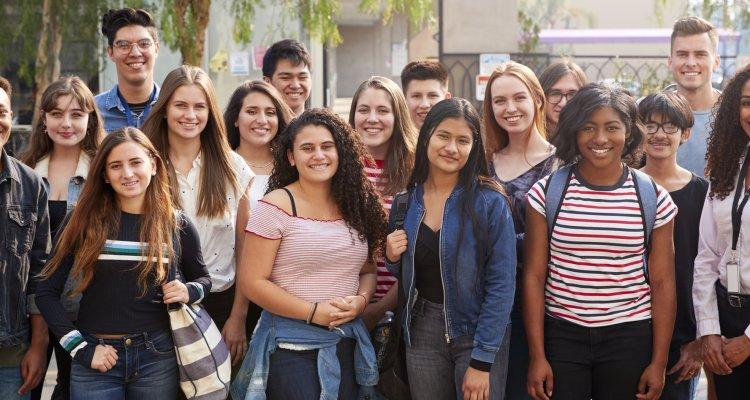 Jovens na univesrsidade olhando para a frente e sorrindo.