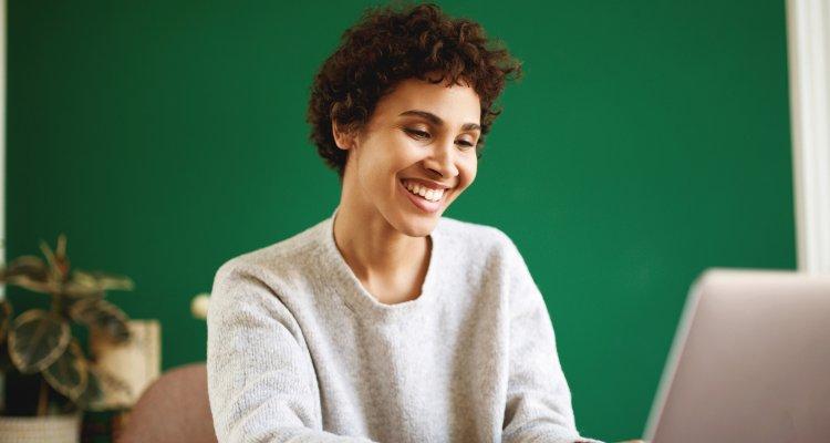 Mulher jovem olhando emocionada para o seu notebook