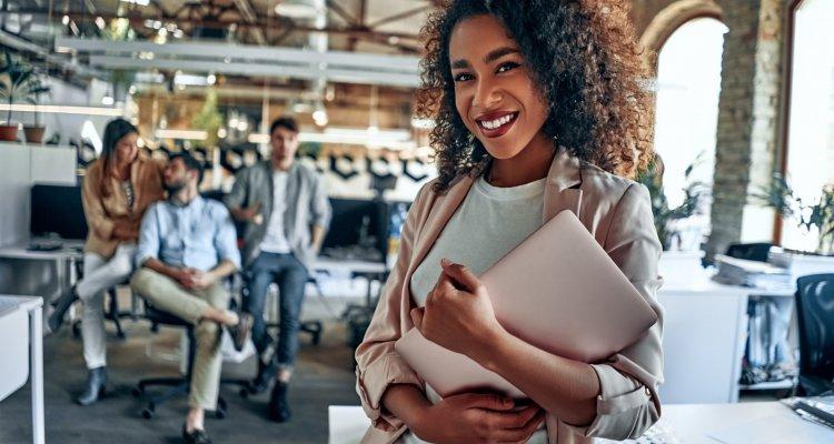 Jovem líder negra segura um computador no primeiro plano, ao fundo, colegas de trabalho conversam