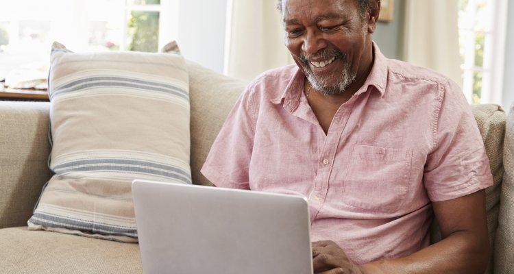 Homem trabalhando sorridente no sofá de casa