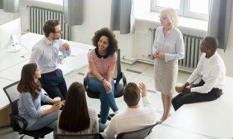Uma roda de executivos de diferentes etnias, gêneros e idades debate aspectos do human experience management