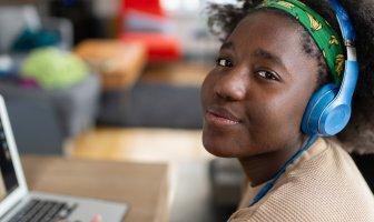 Jovem negra trabalhando com fone de ouvido azul e usando uma faixa verde de cabelo