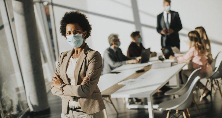 Executiva negra com braços cruzados usando máscara para sobreviver ao coranavírus. Ao fundo, outros executivos estão ao redor da mesa também com máscaras