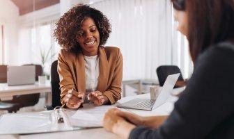 Recrutadora negra observa documentos em uma pasta em cima da mesa enquanto entrevista candidata
