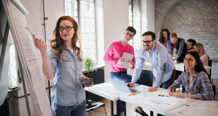 Jovem profissional ruiva aponta com uma caneta para um flipchart com tendências de RH para 2021, ao fundo, colegas de trabalham a observam