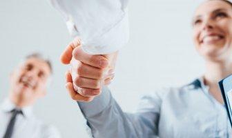 Pessoas dando as mãos durante entrevista de emprego
