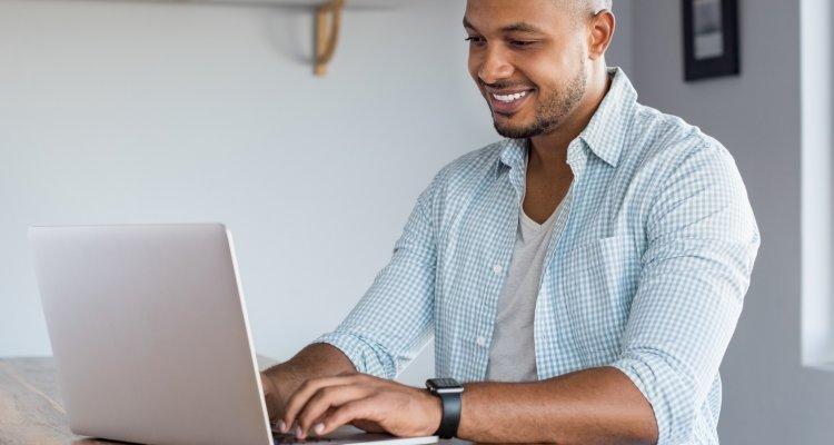 Homem de camisa azul clara trabalhando em seu notebook de casa