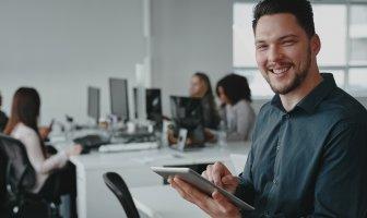 Homem sorridente olhando para frente com tablet na mão