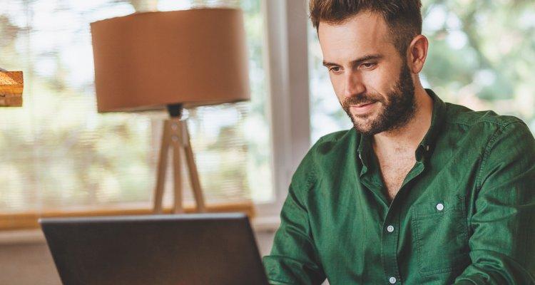 Homem com camisa verde digitando no notebook em sua casa