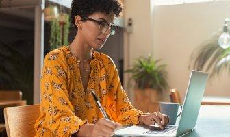 Executiva com vestido amarelo florido atenta na tela do computador às dicas de abono pecuniário