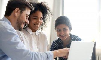 Colaboradores felizes observando ferramentas online para contratar melhor
