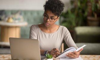 Recrutadora negra observa na tela de seu computador a diferença entre plataforma de recrutamento e software