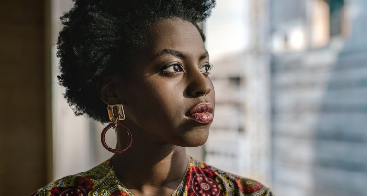 Mulher negra pensativa olhando para o lado