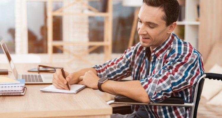 Homem cadeirante trabalhando no escritório e fazendo anotações em um bloco