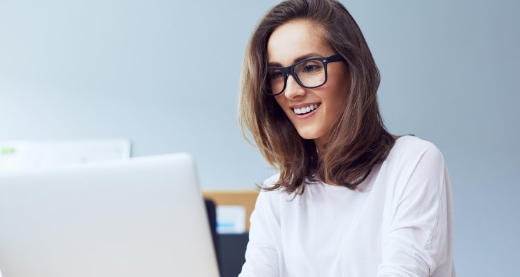 Mulher sorrindo ao digitar no notebook