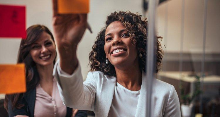 Duas mulheres fazendo dinâmica em post its no trabalho