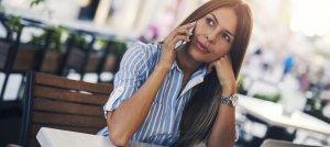 Mulher no celular aparentando escutar a conversa com atenção