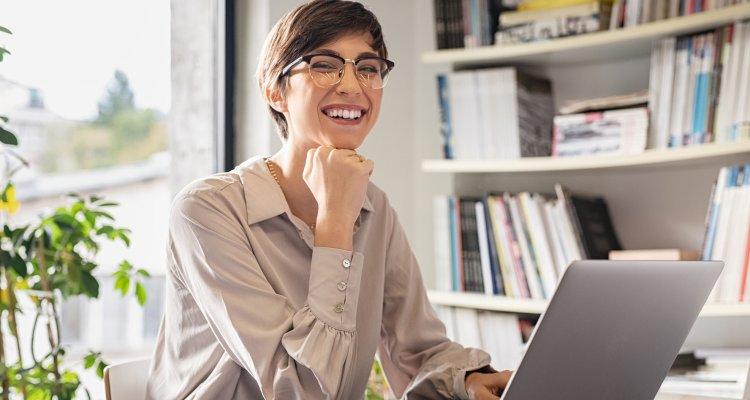 Mulher sorridente em frente ao notebook