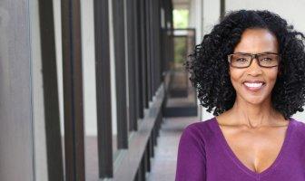 Mulher negra com blusa roxa e oculos olhando para a frente com um sorriso no rosto