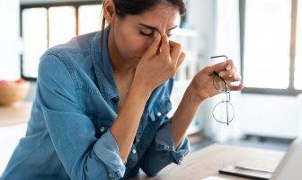Mulher jovem com expressão de cansada trabalhando da sua casa
