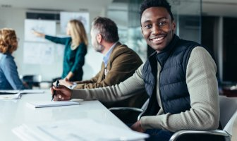 profissional negro segura uma caneta ao fundo outros executivos discutem como nao afastar talentos