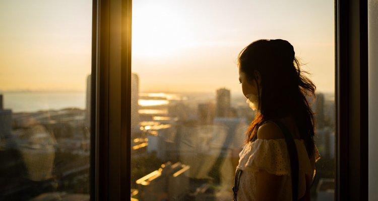 Profisisonal em seu home office buscando conexão humana pela janela
