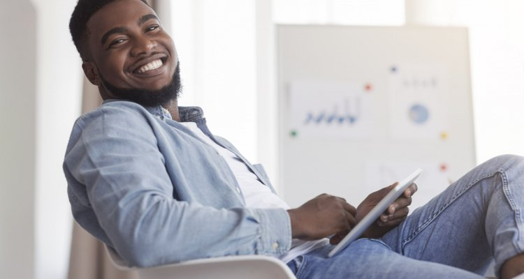 Um candidato negro sentando e sorrindo, esperando sua chance para ser um dos melhores talentos da empresa