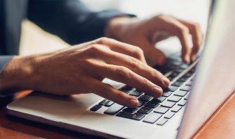 Mãos digitando em um teclado de notebook